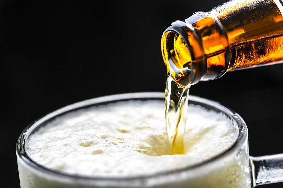 remplissement d'un verre de bière avec bouteille